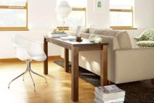 14 a narrow wooden desk placed behind the sofa and a chair plus a lamp that match the organic decor