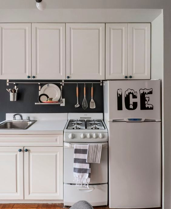 a traditional white kitchen with a chalkboard backsplash that features a holder for cook ware