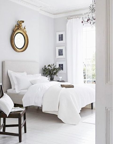 an airy and neutral space with sheer curtains, crispy white bedding and some darker touches for depth