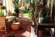 15 a boho porch with a rattan bench, a lot of baskets, a printed boho rug, woven lanterns and much greenery