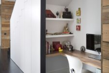 15 a contemporary home office space built inside a staircase with a built-in desk, shelves and a chair