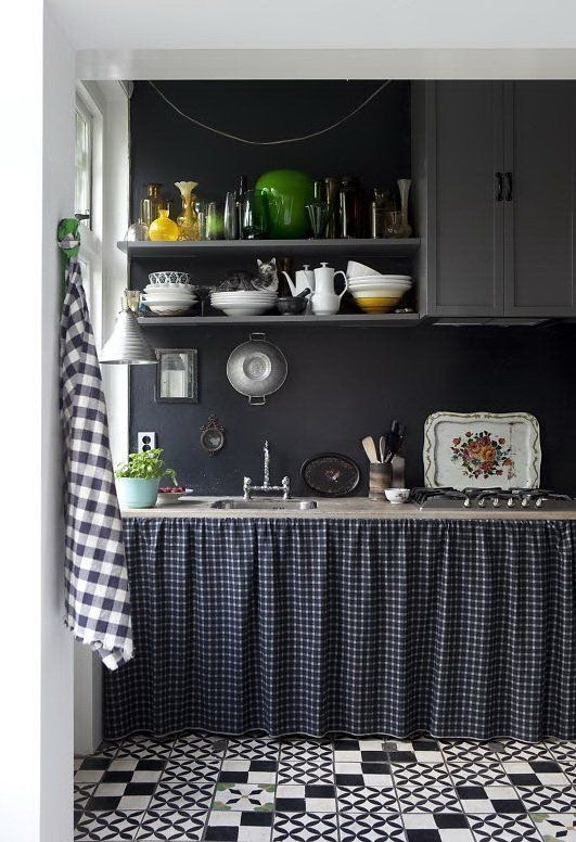 a vintage grey kitchen with a chalkboard backsplash that brings drama to the space