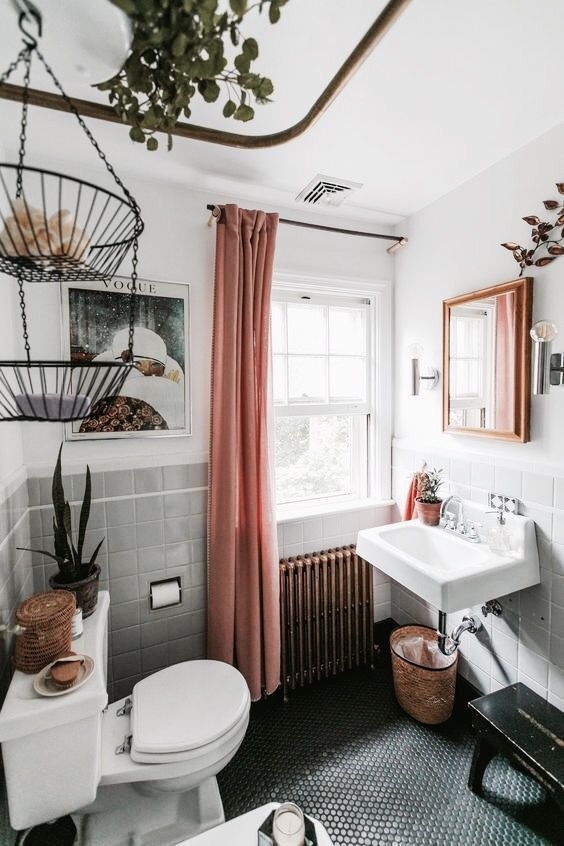 baskets, penny tiles on the floor, potted plants and greenery and a metal hanging shelf make the space boho
