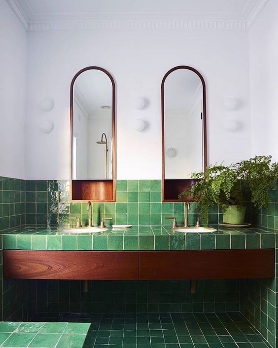 glossy green tiles with a texture and rich wood plus potted greenery for a luxurious and relaxing space
