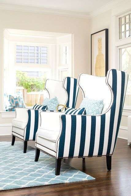 spruce up your vacation home with such creative wingback chairs with a white top and striped backs with a nail trim