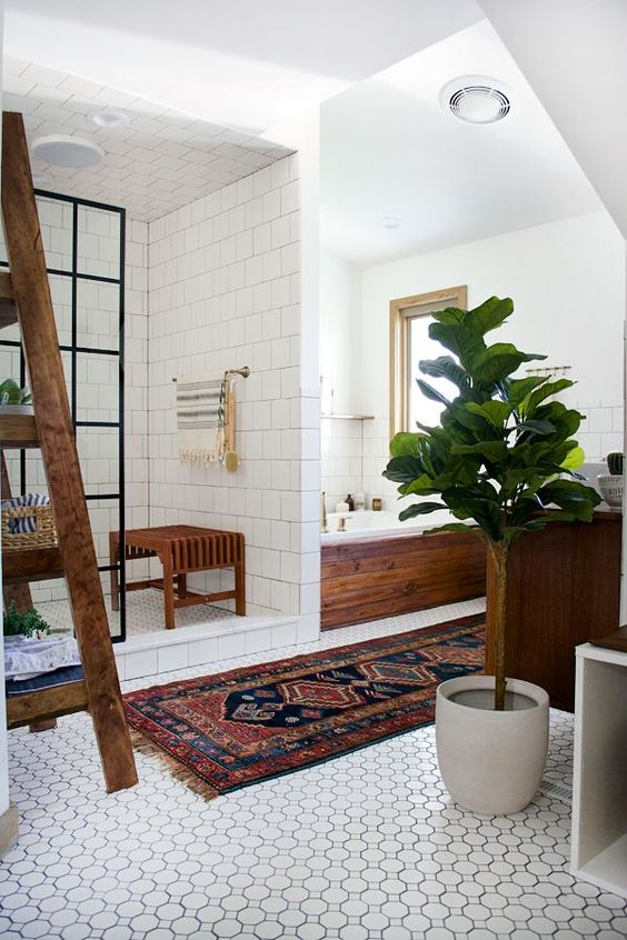 a boho chic space with white tiles, potted greenery, wooden touches and a boho rug