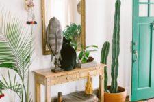 16 a boho rug, a console, a stool, a mirror, some plants and a cactus plus folk decor for a boho feel