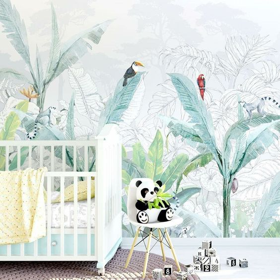 a fun tropical nursery with a creative watercolor tropical statement wall, colorful bedding and a panda toy