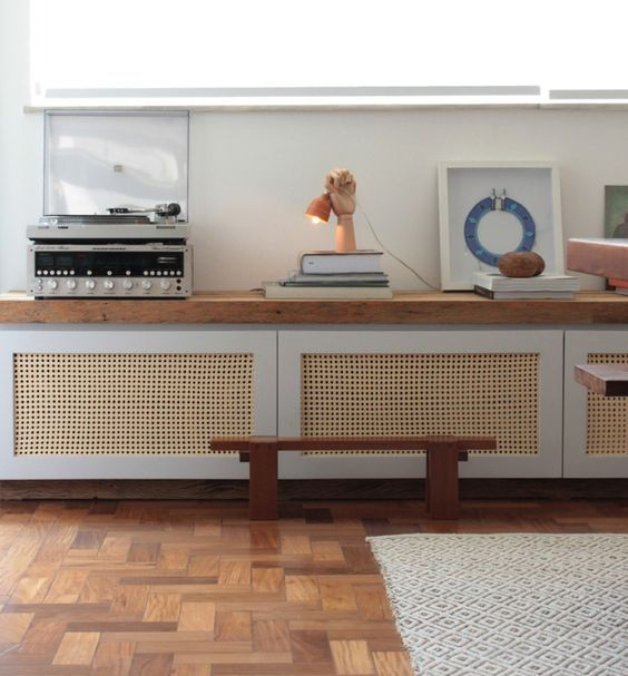 a long storage unit with wood lettice doors and a wooden countertop for a mid-century modern feel