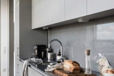 16 a minimalist grey kitchen with a concrete backsplash covered with a glass screen completely for keeping it clean