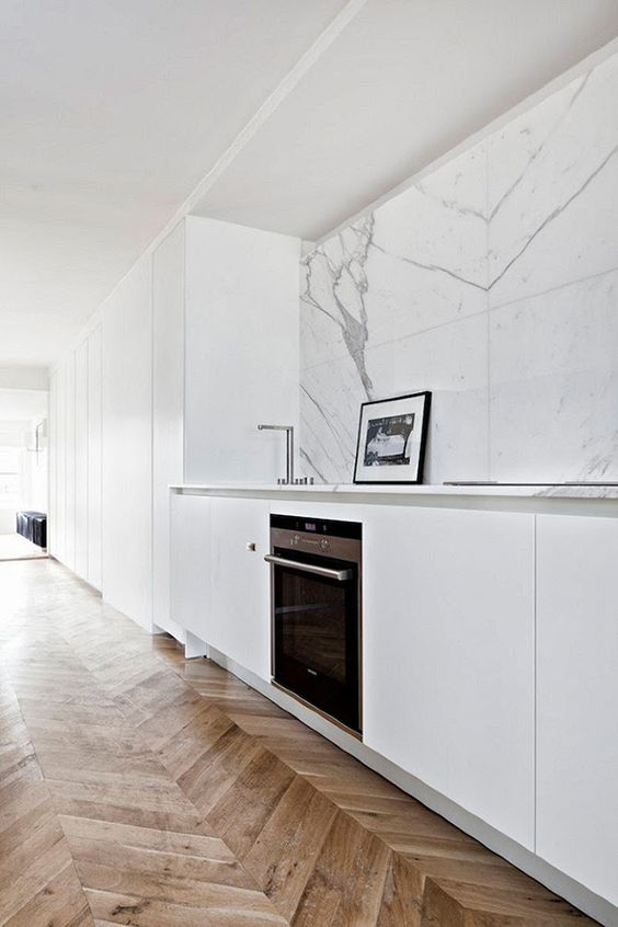 a minimalist white kitchen with a white marble tile backsplash and touches of grey for a chic look