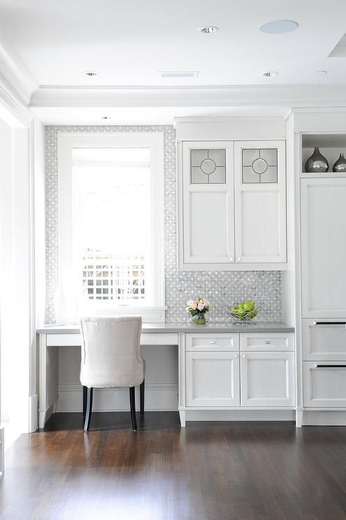 a serene white kitchen with a built-in office nook with printed wallpaper to highlight it and a comfy upholstered chair