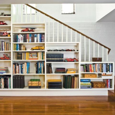 a traditional staircase with an open bookcase - just place a chair in front of it and voila
