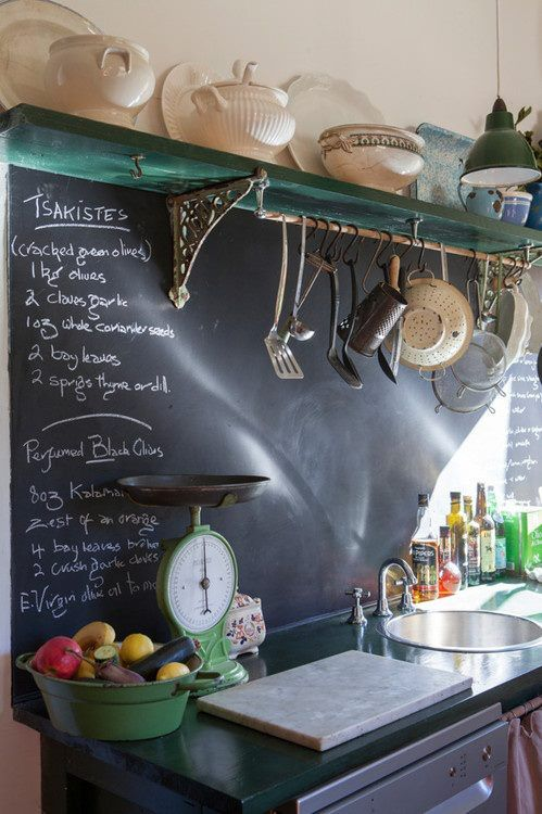a vintage space with dark shabby shelves and countertops and a chalkboard backsplash