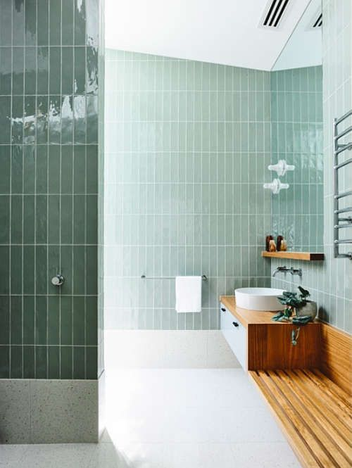 glossy pale green tiles and warm colored wood create a very natural space with a calming effect