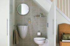 16 grey tiles, white walls and a small shelf – this powder room accomodates everything necessary
