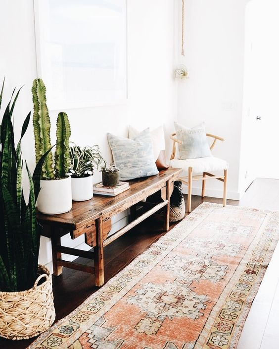 a boho rug, a vintage wooden bench, a chair, pillows and cacti and succulents in pots
