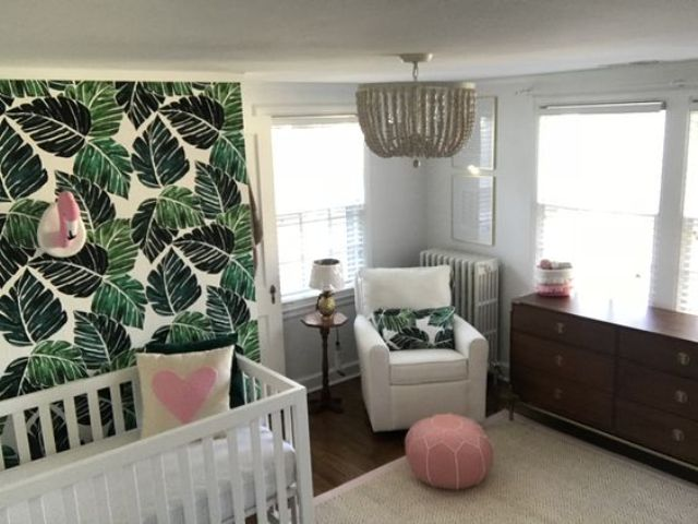 a cool nursery with a leaf print wall, pink touches and a flamingo head and a glam chandelier