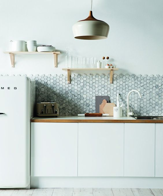 a minimalist white kitchen with wooden touches and a grey marble hexagon tile backsplash