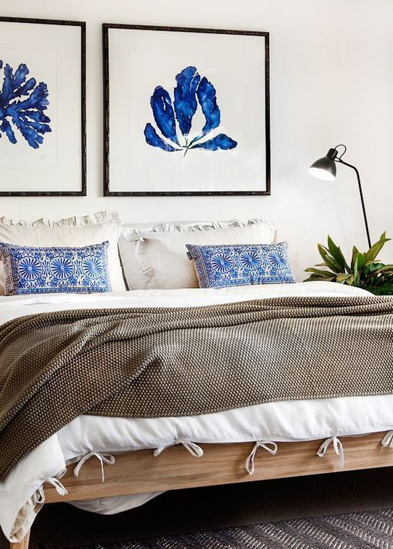 a textural bedspread, pritned pillows and bold blue artworks over the bed refresh the neutral space