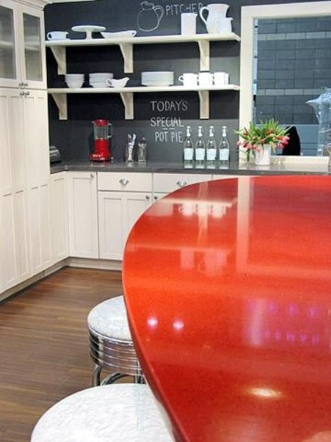 a white kitchen, a chalkboard backsplash and a red dining table for a bold look