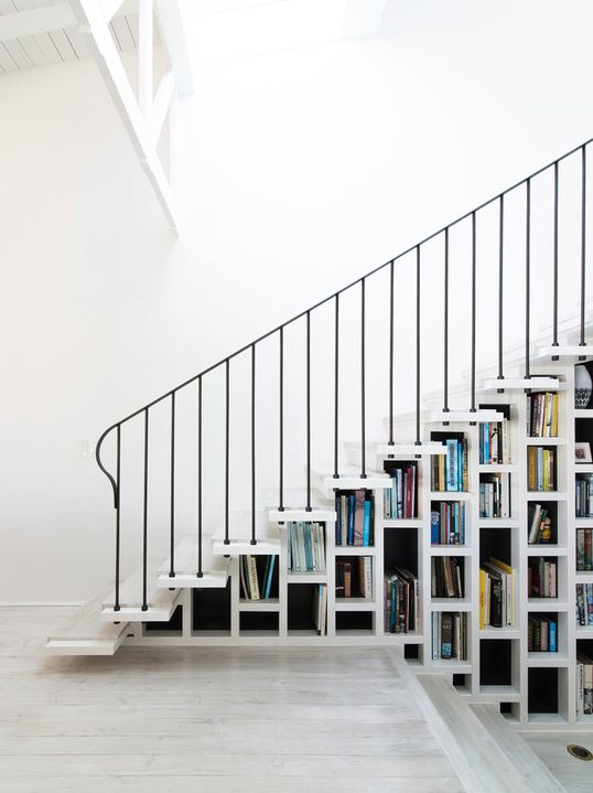 a white staircase that acts as a bookcase is all you need to save a lot of space in your home