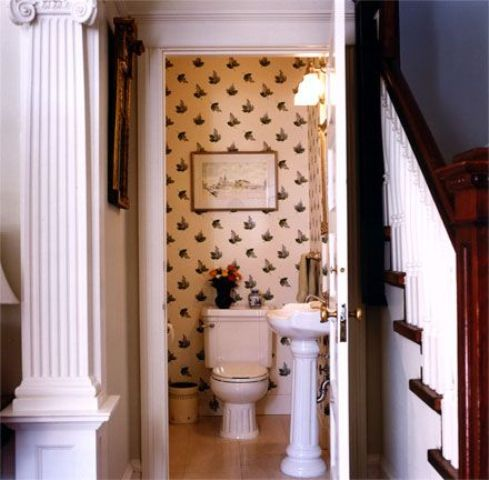 vintage printed wallpaper and aartworks make the powder room connected to the living room