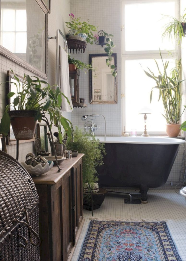 a boho bathroom as a greenery oasis with white tiles, wooden furniture and a woven chest for towels