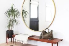 18 a boho rug, a wooden bench, an oversized round mirror, a potted plant