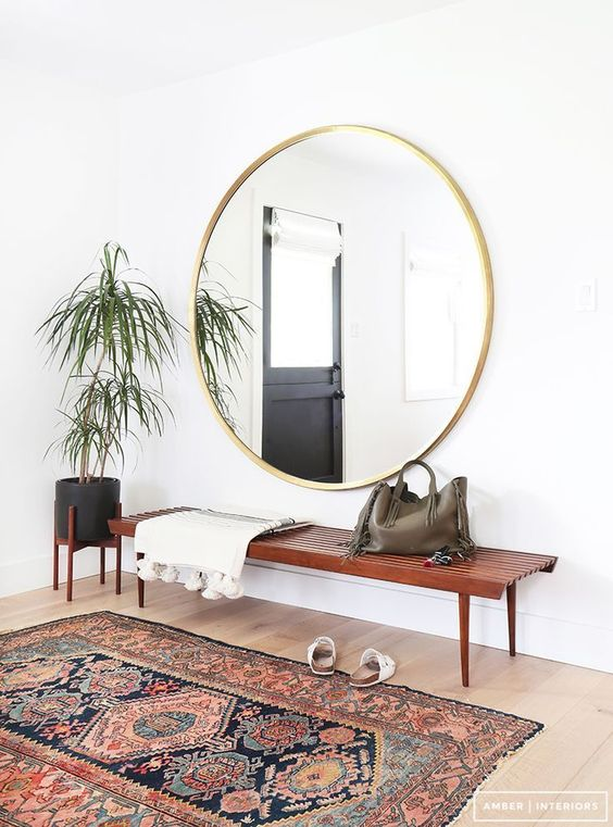 a boho rug, a wooden bench, an oversized round mirror, a potted plant