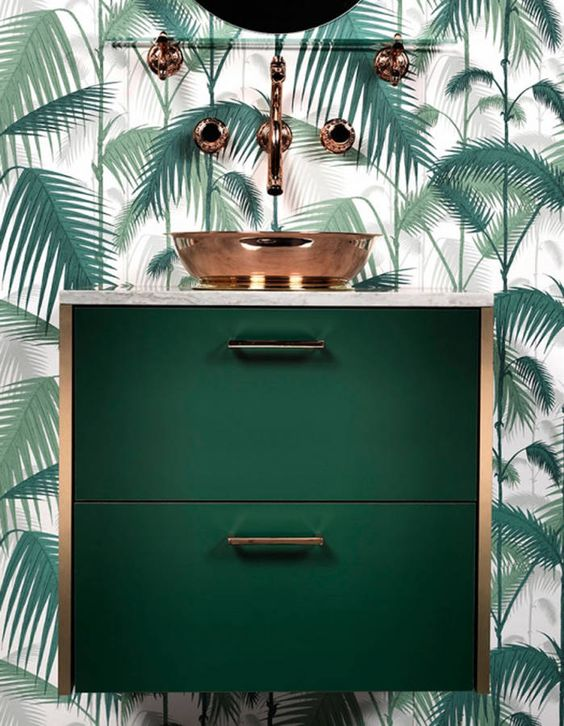 a chic dark green floatign vanity with copper touches and a palm leaf wall for en elegant look