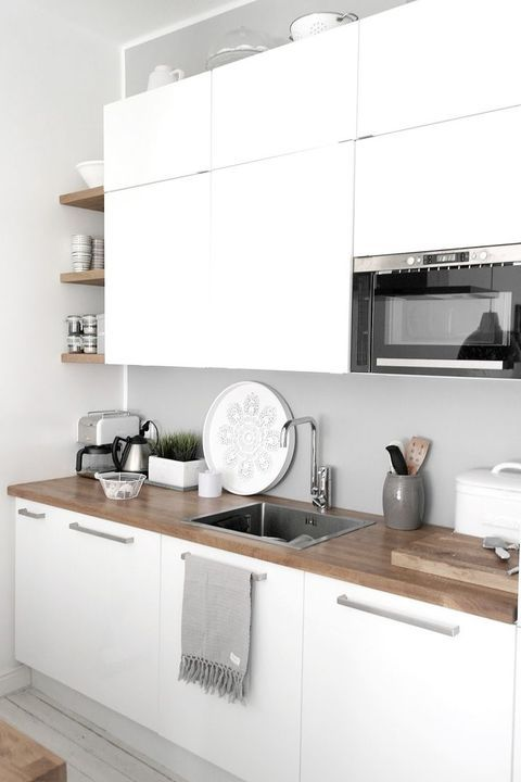 a minimalist white kitchen with a wooden countertop and a sleek concrete backsplash for an edgy feel