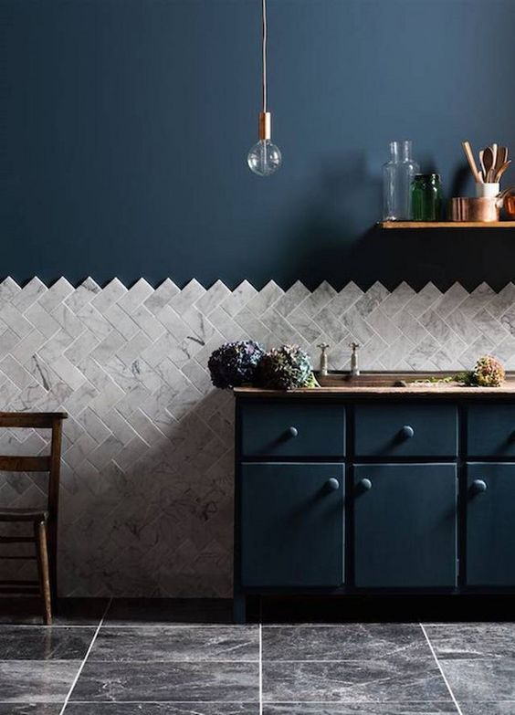 a navy kitchen with copper touches, wood and a grey marble chevron clad backsplash that adds interest