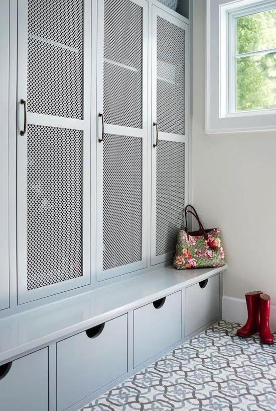 a traditional mudroom with a large closet unit with wood lattic doors to let the air in