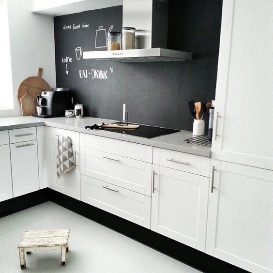 a white Scandinavian kitchen with a chalkboard backsplash that contrasts and adds depth to the space