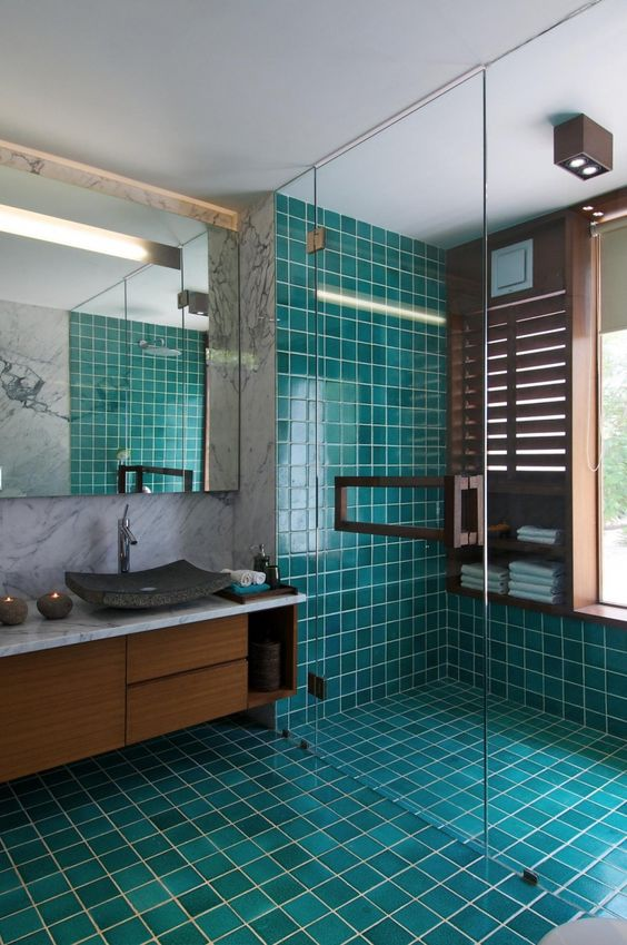 turquoise and teal tiles covering the floor and the shower contrast the rich shades of wood and create a mood