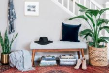 19 a boho rug, an upholstered bench, potted plants, some books under the bench