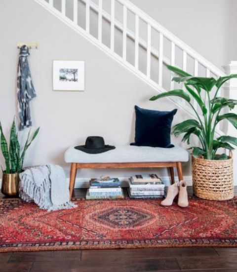 a boho rug, an upholstered bench, potted plants, some books under the bench