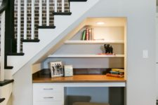 19 a little built-in home office nook with a built-in desk and shelves and lights and a small stool
