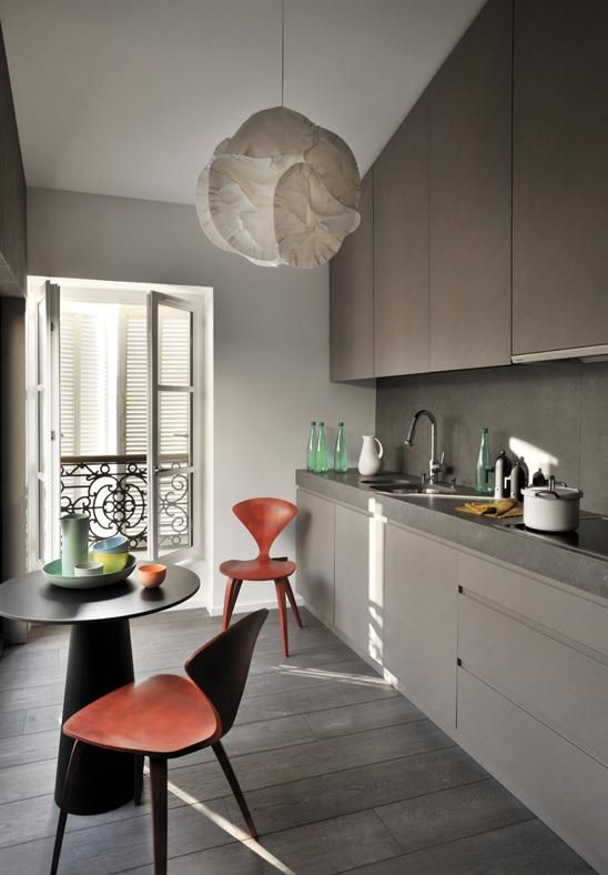 a moody taupe kitchen with a grey concrete backsplash and countertops to polish the look