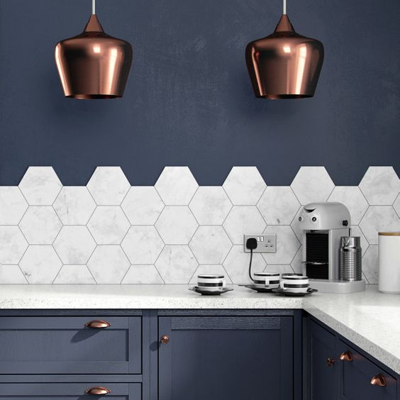 a navy kitchen with elegant copper touches and marble hexagon tiles on the backsplash that add a refined feel