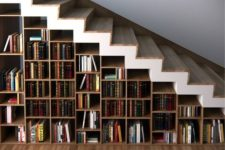 19 a whole under stairs bookcase features many books and can hold some other objects, too