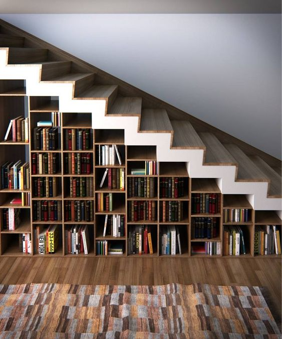 a whole under stairs bookcase features many books and can hold some other objects, too