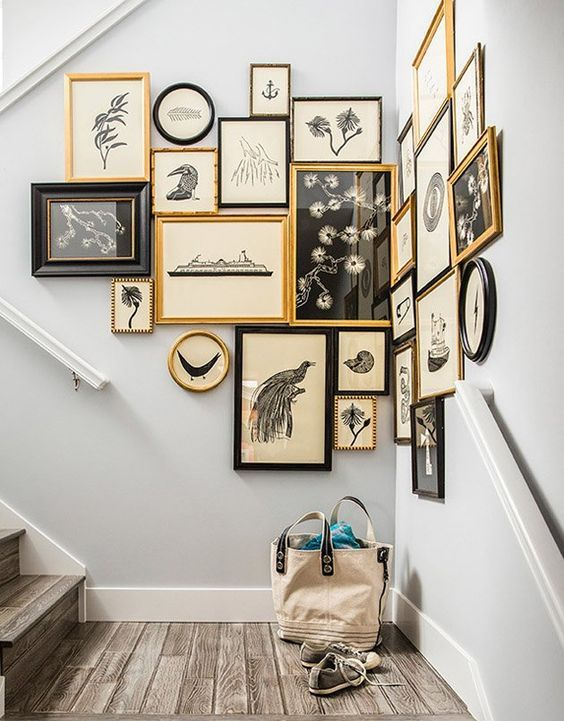 an awkward nook on the stairs is taken by a gorgeous gallery wall in black and gold
