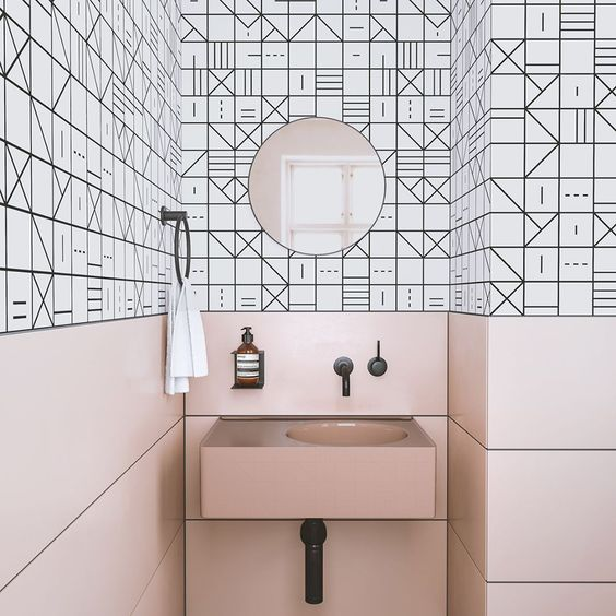 pink panels and a sink contrast the geometric black and white tiles and create a unique space