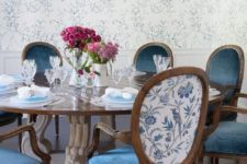 19 refined vintage chairs with blue velvet seats and floral printed fabric on the backs to match the wallpaper