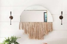 20 a boho space with a woven bench, a woven basket, a mirror with fringe and a potted plant