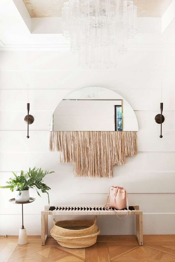 a boho space with a woven bench, a woven basket, a mirror with fringe and a potted plant