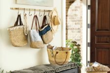 20 a coastal entryway with a watercolor boat artwork, an upholstered bench, some straw bags as part of decor