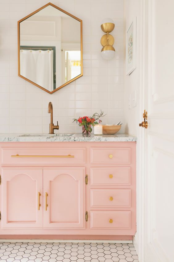 a light pink sink console with a marble top and gold handles and knobs are ideal for a glam bathroom look